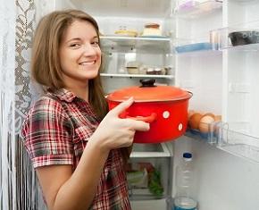 Девушка ставит кастрюлю в холодильник