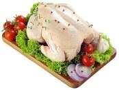 Тушка курицы на доске с овощами
