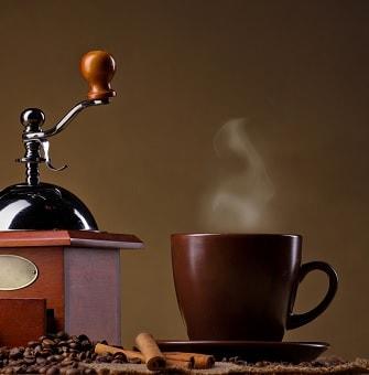 Чашка с ароматным напитком и кофемолка
