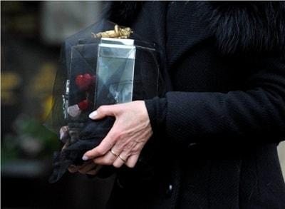 Женщина держит в руках урну с прахом